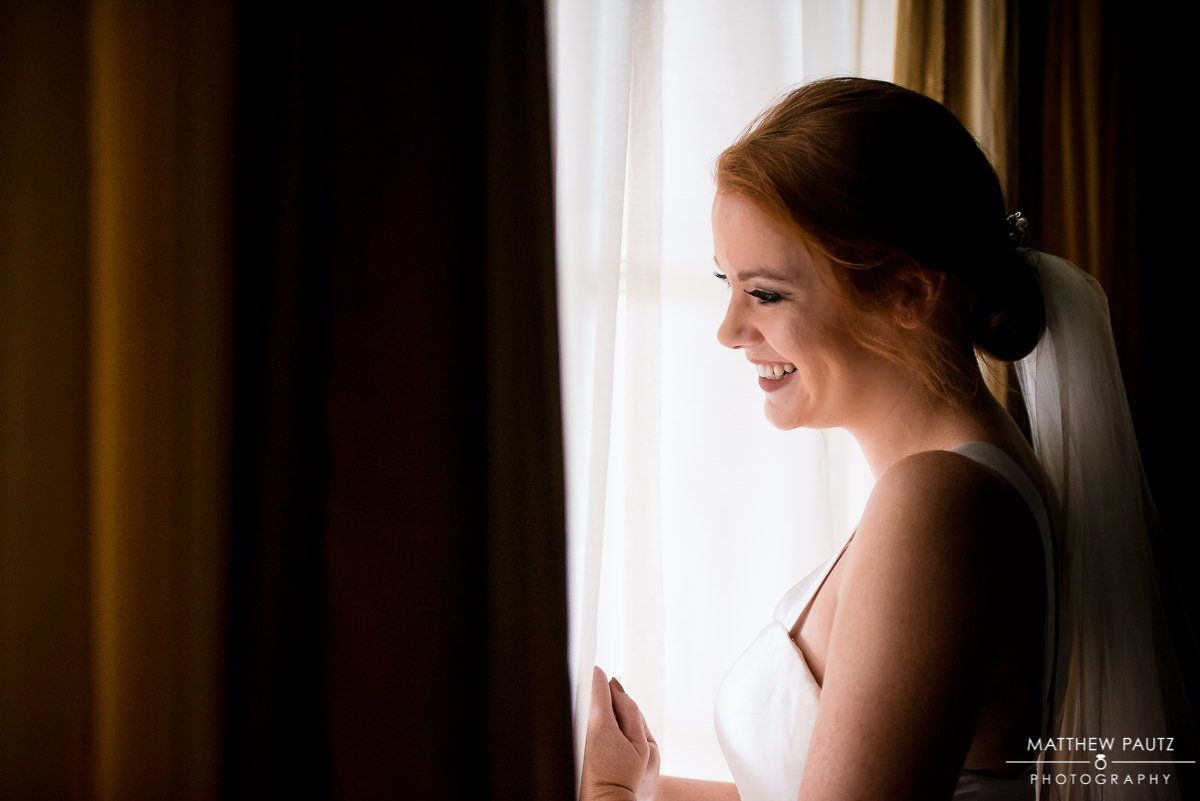 bride laughing in front of window
