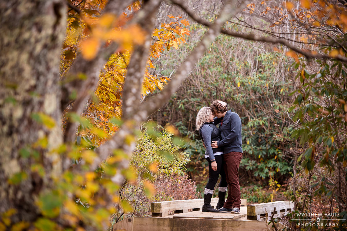 Couple kissing on a footbridge in the mountains during Fall color