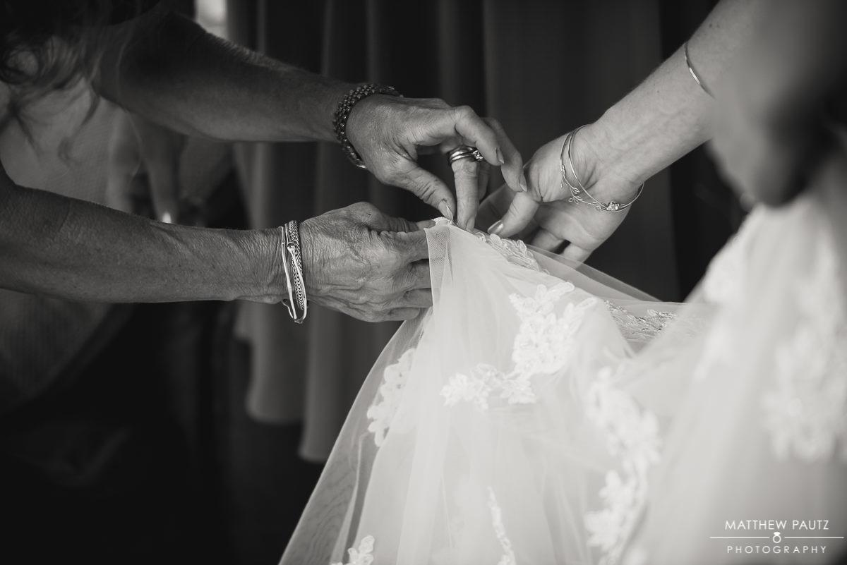 Mother of bride adjusting wedding dress details