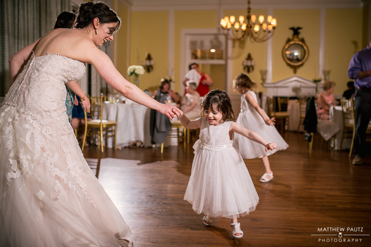 bride dancing with flower girl at wedding reception