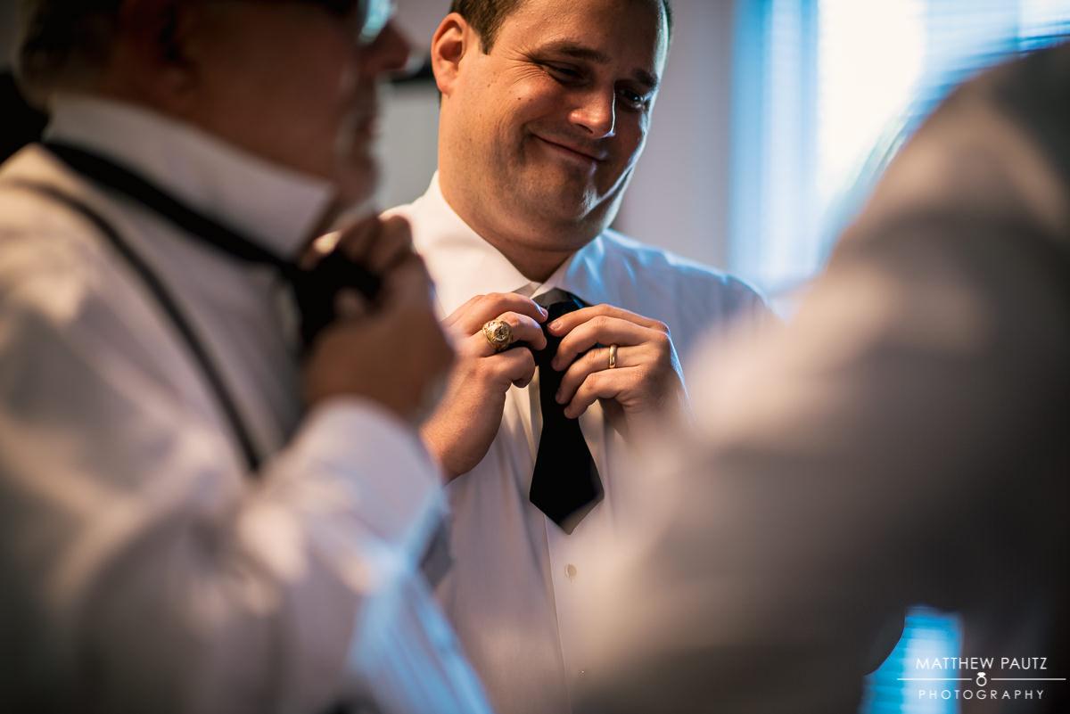 groomsmen tying bowties before wedding