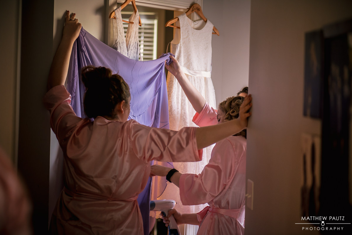 bridesmaids steaming dresses before ceremony