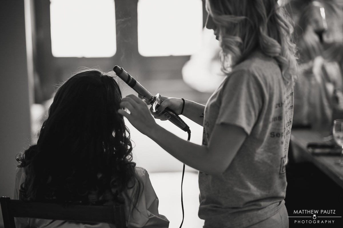 silhouette of bridesmaid getting hair styled before ceremony