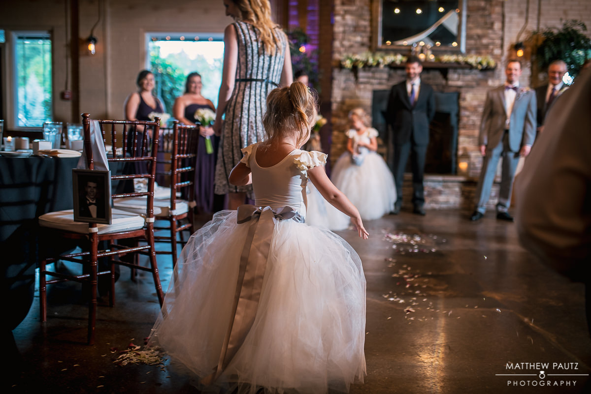 flower girl dropping petals at wedding ceremony at larkins sawmill