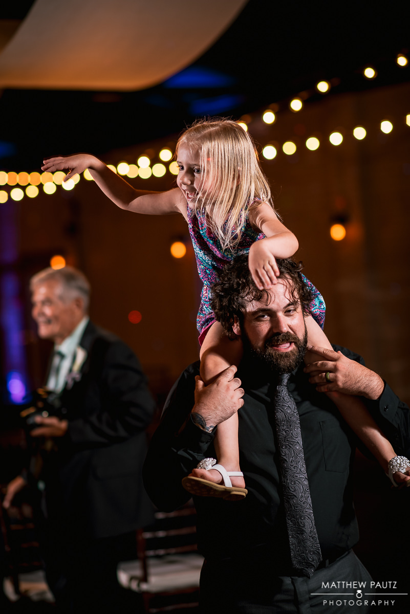 wedding guest with child on shoulders dancing at reception