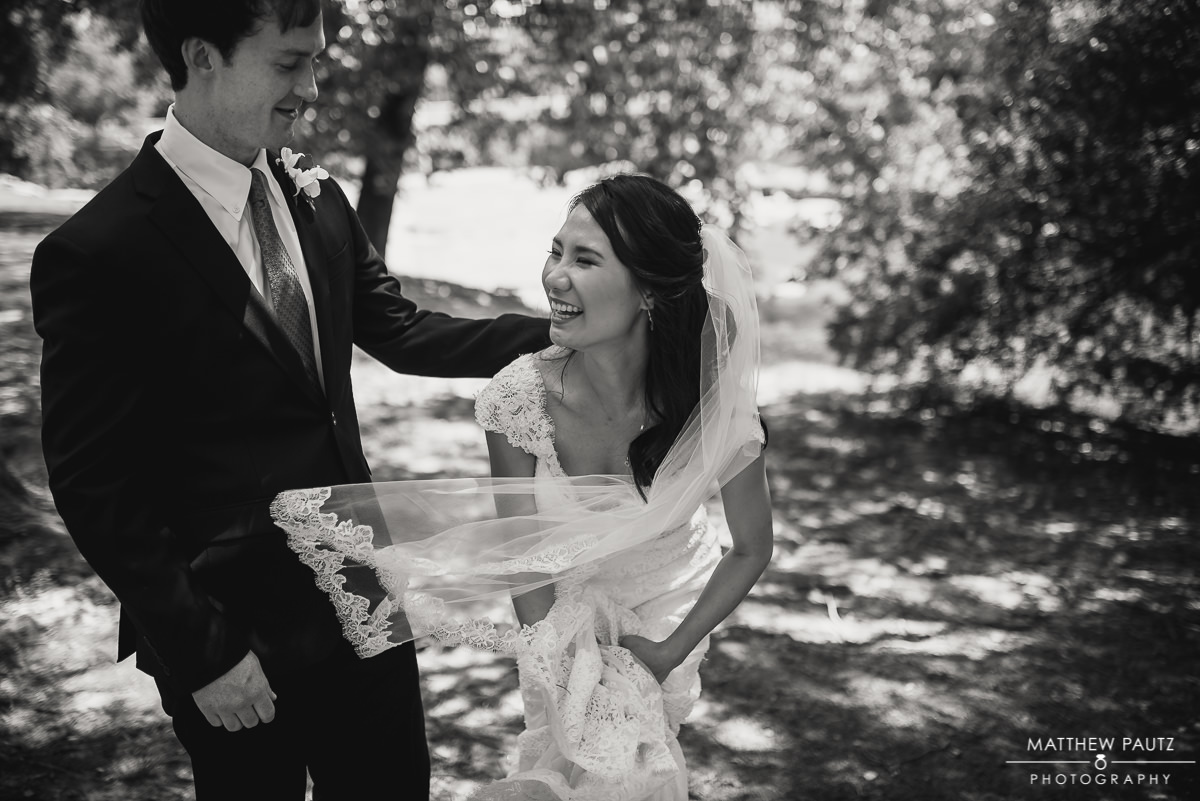 bride and groom laughing and having fun outside at Greenville's Falls Park