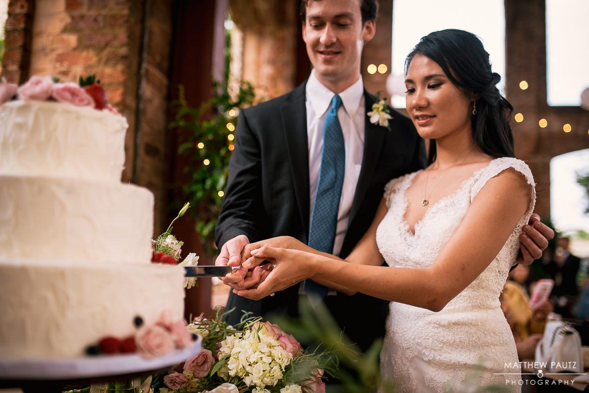 Bride cutting wedding cake with groom