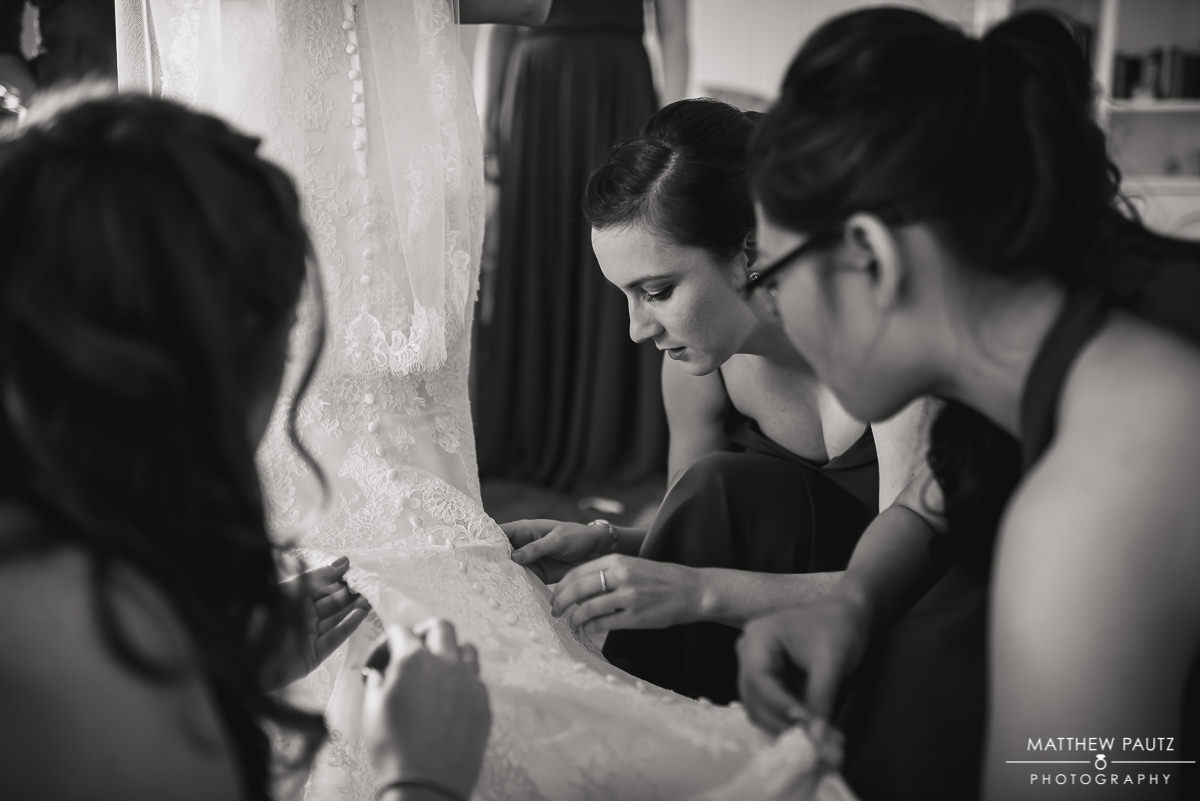 bridesmaids fixing bride's wedding dress before ceremony